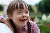stock photo of playgroup  - Portrait of beautiful young girl smiling outside - JPG