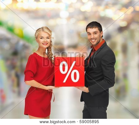 sale, shopping and mall concept - smiling man and woman with percent sign at shopping mall