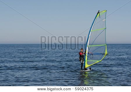 BAIKAL, RUSSIA - SEPT 25, 2012: Unidentified teenager of windsurfing sailor  on September 25 2012 in Baikal lake, Russia. Lake Baikal - largest natural fresh water reservoir, tourist center of Russia.