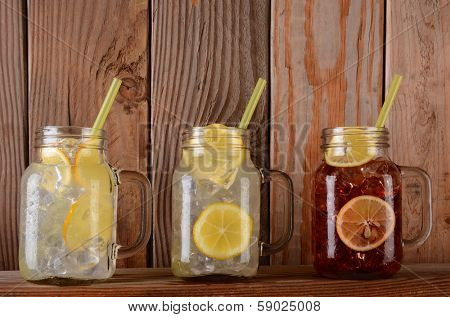 Glasses of lemonade and fruit juice on a rustic kitchen ledge. The mason jar style glasses have handles and drinking straws.