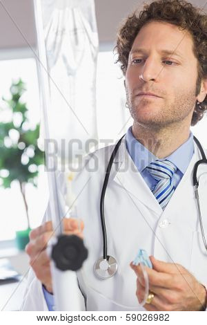 Male doctor adjusting IV drip in hospital