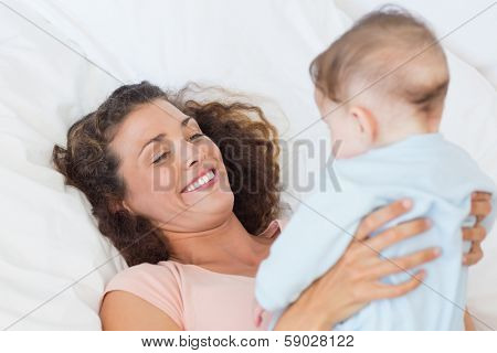 Smiing mother playing with baby boy in bed