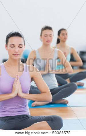 Sporty young women in Namaste position with eyes closed at a fitness studio