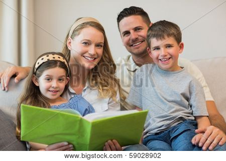 Happy family with photo album sitting on sofa at home