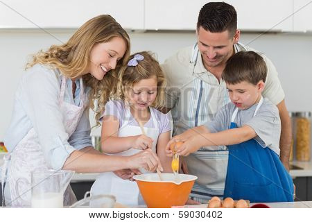 Happy family mixing egg to bake cookies in kitchen