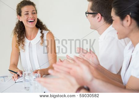 Business people applauding for businesswoman after presentation in office