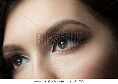 Closeup of beautiful woman eye with makeup, looking up