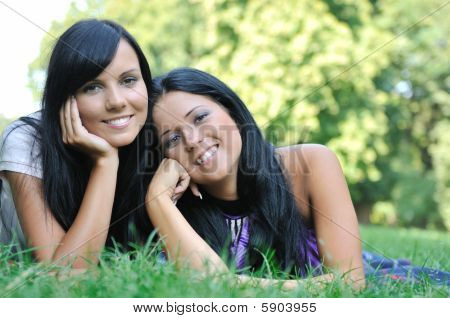 Two Happy Sisters Lying Outdoors In Grass