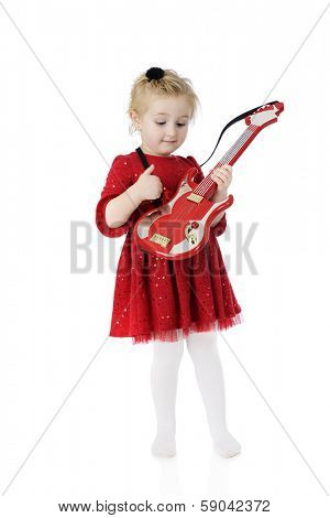 An adorable dressed-up preschooler, happily strumming her toy guitar.  On a white background.  Motion blur on right hand.