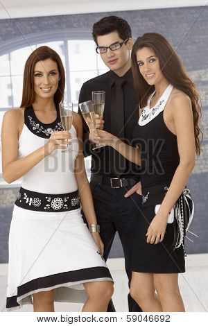 Elegant young companionship drinking champagne, clinking glasses.