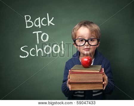 Young child holding stack of books and back to school written on chalk blackboard poster