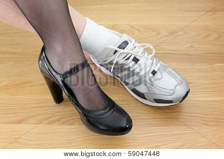 Woman wearing one business shoe and sports shoe concept for work-life balance, healthy lifestyle and wellbeing choice