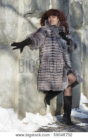 The Attractive Woman In A Fur Coat From The Silver Fox Is Photographed At A Stone Wall.