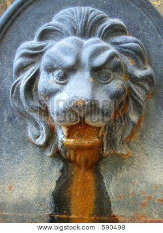 Old Iron Fountain In Shape Of Lion's Head Showing Rust And Other Weathering Effects Of The Elements
