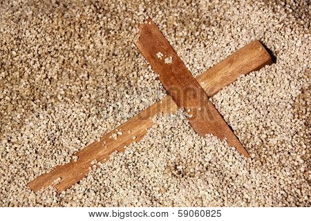 Forgooten Wooden Cross On Sand Texture Background