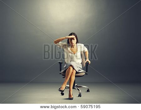 serious businesswoman attentively peered at something over dark background