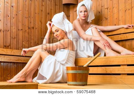 Two Women in sauna of wellness spa relaxing , enjoying an infusion