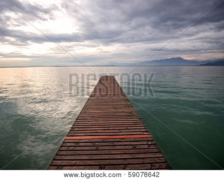 Desolate wooden footbridge on a lake in the morning
