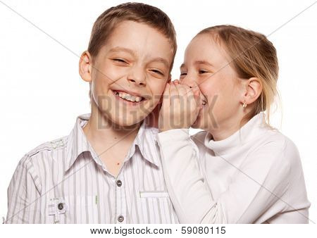 Girl whispers boy in the ear secret. Children gossip