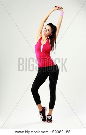 Young beautiful woman stretching her arms above her head on gray background