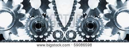 gears and cogwheels of titanium and steel powered by a timing-chain, panoramic view