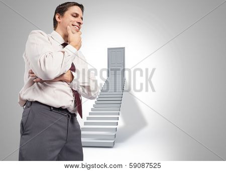 Thoughtful businessman with hand on chin against shut door at top of steps