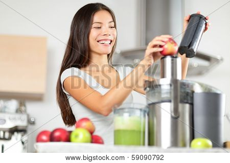 Juicing - woman making apple and green vegetable juice using juicer machine at home in kitchen. Healthy eating happy woman making green vegetable and fruit juice. Mixed race Asian Caucasian model.