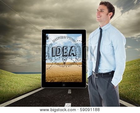 Smiling businessman standing with hand in pocket against highway under cloudy sky