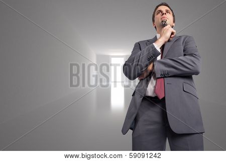 Thinking businessman holding his glasses against bright hall