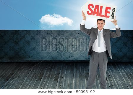 Businessman with sign above his head against sunny sky beyond balcony
