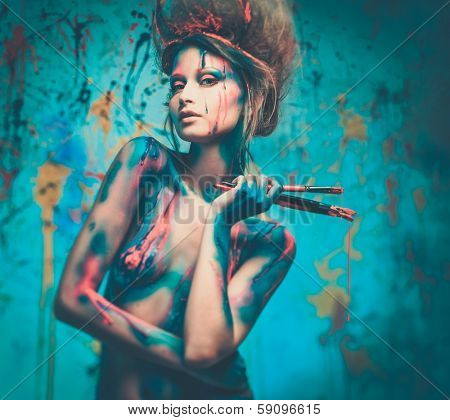 Young woman muse with creative body art and hairdo holding paint brushes