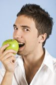 Young Man Taking Bite Of Green Apple
