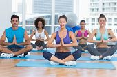 foto of namaste  - Sporty young people in Namaste position smiling at a bright fitness studio - JPG