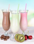 stock photo of fruit shake  - Milk shakes with fruits on table on light blue background - JPG