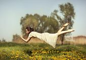 stock photo of gravity  - Girl in pajamas night flying over the field and smelling dandelions - JPG