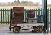 stock photo of carry-on luggage  - Vintage Cases on a Traditional Railway Luggage Trolley.