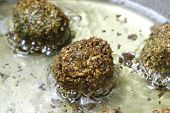 Homemade falafel mixture frying in oil. The balls comprise crushed soaked chickpeas, parsley and cor
