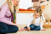 stock photo of spinner  - Girl sitting with mother on floor playing with wooden toy spinner - JPG