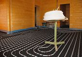 stock photo of floor heating  - A hydronic closed loop underfloor heating system laid out on molded insulated panel in EPS with a spooling table inside a partially constructed wooden house - JPG