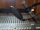 pic of recording studio  - a studio vocal microphone over a mixing board console