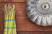 fresh green asparagus and a steamer basket on red rustic barn wood table