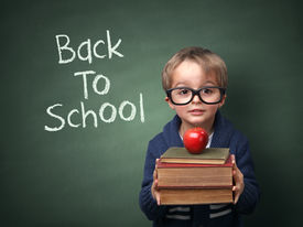 picture of child development  - Young child holding stack of books and back to school written on chalk blackboard - JPG