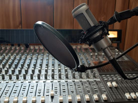 pic of recording studio  - a studio vocal microphone over a mixing board console  - JPG