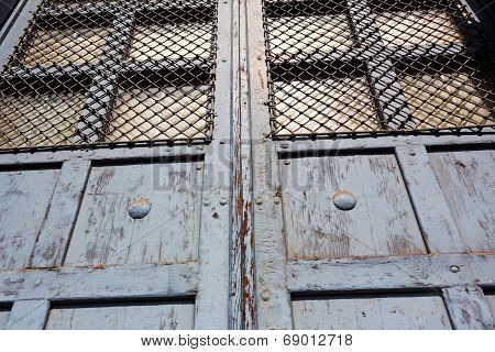 Old Door With Bars In The Sunshine