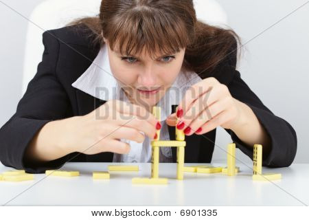 Woman Are Concentrated In Building A Tower On Table With Domino