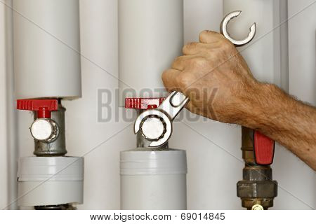 Man Is Working On Heating Pipes