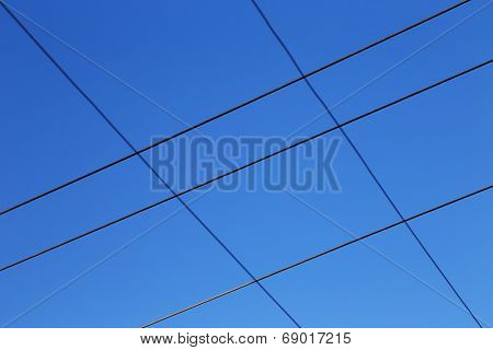 High tension wires against the blue sky