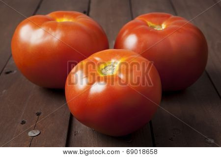 Three Tomatoes On Brown Table