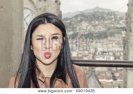 Girl in balcony with city behind her