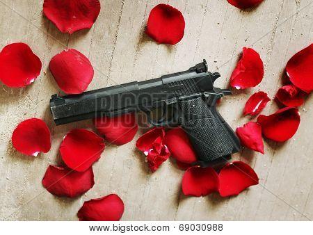 Black gun red roses petals on the floor